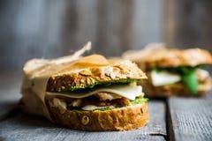 Sandwich met graangewassenbrood, kip, pesto en kaas op de rustieke houten achtergrond Stock Fotografie
