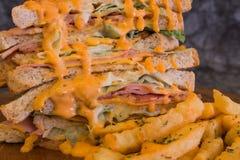 Sandwich met kruidige saus en Frieten op houten plaat Royalty-vrije Stock Foto