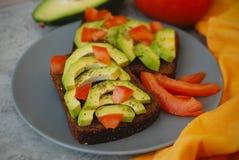 Sandwich mit Avocado und Tomaten und Gewürze in Gray Plate und orange Serviette - gesundes Frühstücks-Konzept Lizenzfreies Stockfoto