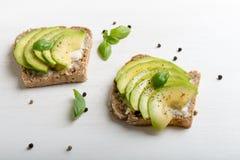 Sandwich mit Avocadoscheiben und -basilikum stockfotografie