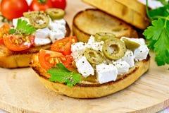 Sandwich mit Feta und Oliven auf hölzernem Brett Stockfoto