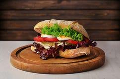 Sandwich mit Gemüse und Eiern auf Schneidebrett auf dunklem woode Lizenzfreie Stockbilder