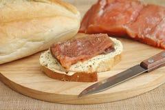 Sandwich mit Lachsen auf Schneidebrett Stockfotografie