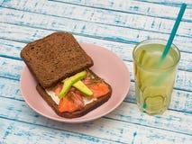Sandwich mit Lachsen, Avocado, Schwarzbrot auf einer Platte und einem Glas Limonade Stockbilder