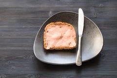 Sandwich mit Pastete und Messer auf Platte auf Dunkelheit lizenzfreie stockfotos