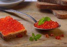 Sandwich mit rotem Kaviar und auf einem Metalllöffel Stockfotografie