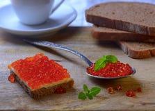 Sandwich mit rotem Kaviar und auf Metalllöffel Lizenzfreies Stockbild