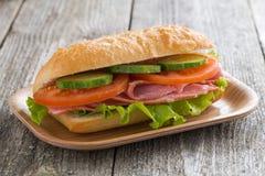 Sandwich mit Schinken und Gemüse auf Holztisch, Nahaufnahme Stockfotos