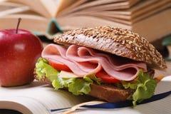 Sandwich mit Schinken und Gemüse und roter Apfel auf offenem Notizbuch Stockfotos