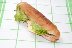 Sandwich mit Schinken und Salat auf einer grünen Tischdecke Lizenzfreies Stockfoto
