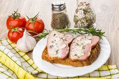 Sandwich mit Speck und Knoblauch in der Platte Rote Tomaten, Rosmarin Stockbilder