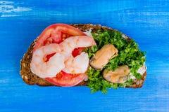 Sandwich mit Tomate, Garnelen, Miesmuscheln und gehackter Petersilie auf a Stockbild