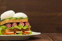 Sandwich mit Tomaten, Gurken, Würsten, Salat und Eiern Lizenzfreie Stockfotos