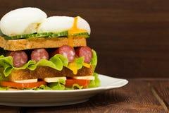 Sandwich mit Tomaten, Gurken, Würsten, Salat und Eiern Lizenzfreie Stockbilder