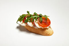 Sandwich with mozzarella, red tomato and arugula on white background. Sandwich with mozzarella, tomato and arugula on white background Stock Image