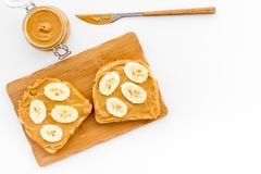Sandwich with nut butter and banana for breakfast on white background top view copy space Royalty Free Stock Photos