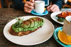 Free Sandwich Or Toast With Avocado In The Foreground. A Person Is Going To Eat It And Drink Coffee Or Tea Stock Photos - 121558273