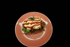 Sandwich on orange plate in black background royalty free stock images