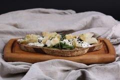 Sandwich ou bruschette de Rye avec du fromage de ricotta, les artichauts marinés et l'arugula sur un conseil en bois, foyer sélec photographie stock