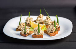 Sandwich with pate, green onion decorated lemon on white plate Stock Image