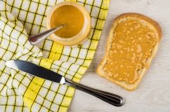 Sandwich with peanut butter, jar with butter and teaspoon, knife. On wooden table. Top view Royalty Free Stock Images