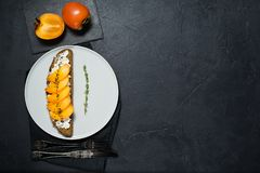 Sandwich with persimmon and soft cheese on a black background with space for text. stock photos