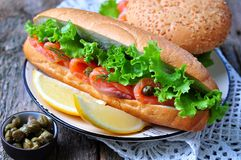 Sandwich with pickled salmon, lettuce, white onion and capers Royalty Free Stock Photos