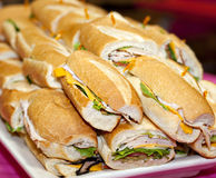 Sandwich platter. A sandwich tray holds a pile of turkey and roast beef sandwiches on kaiser rolls.  Dish is white against a bright pink tablecloth Stock Photos