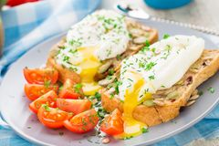 Sandwich with poached egg and cherry tomatoes Stock Photos