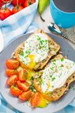Sandwich with poached egg and cherry tomatoes Stock Images