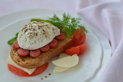 Sandwich with poached egg on white plate near pink napkin close up. Sandwich with poached egg, sausage, cheese, tomato on white plate near pink napkin close up Stock Images