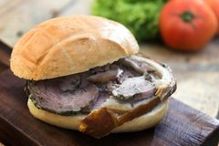 Sandwich with porchetta on cutting board with salad and tomatoes royalty free stock photos