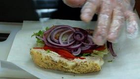 Sandwich praparation. Adding sweet onion and paper