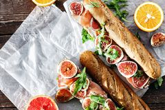 Sandwich prosciutto mascarpone cheese figs wine top view copy space. Sandwich with prosciutto, mascarpone cheese and figs on dark background top view copy space stock images