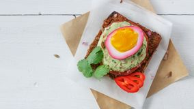 Sandwich with Purple beet pickled eggs, avocado and tomato, copy space. stock image