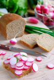 Sandwich with radish and rye bread . Near a loaf of bread, a knife, green onions. The concept of natural organic farm products, stock photo