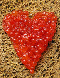 Sandwich with red caviar. Bread with red caviar from heart shape Royalty Free Stock Image