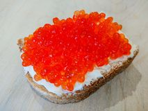 Sandwich with red caviar. White bread with butter. Seafood delicacies Royalty Free Stock Photo