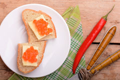Sandwich with red caviar on white plate Royalty Free Stock Image
