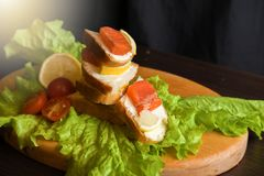 Sandwich with red fish lemon tomatoes and salad on a wooden board stock photos