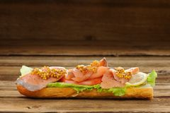 Sandwich with red fish, tomatoes and mustard Stock Photo