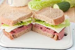 Sandwich with roast beef, cheese, mustard and lettuce on whole wheat italian bread Royalty Free Stock Photos