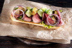 Sandwich with roast beef. On rustic background Stock Images