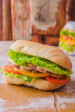 Sandwich with roasted chicken, leaves salad and tomatoes on wooden baskgraund. Selective focus Stock Image