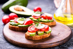 Sandwich with rye bread, avocado, egg, tomato on wooden board Royalty Free Stock Images