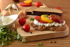 Sandwich of rye bread with cream cheese, tomatoes Stock Photos