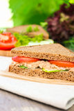 Sandwich with rye brown bread, ripe tomatoes, cucumbers and tuna fish for healthy snack Royalty Free Stock Image