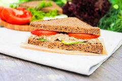 Sandwich with rye brown bread, ripe tomatoes, cucumbers and tuna fish for healthy snack on a napkin on a wooden table Royalty Free Stock Photography