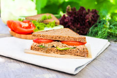 Sandwich with rye brown bread, ripe tomatoes, cucumbers and tuna fish for healthy snack on a napkin on a wooden table Stock Photo