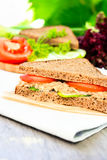 Sandwich with rye brown bread, ripe tomatoes, cucumbers and tuna fish for healthy snack on a napkin on a wooden table Stock Image